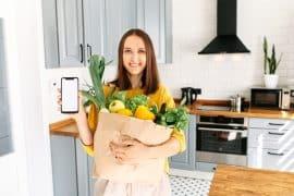 Frau hat gesunde Lebensmittel eingekauft und nutzt eine Ernährungsapp