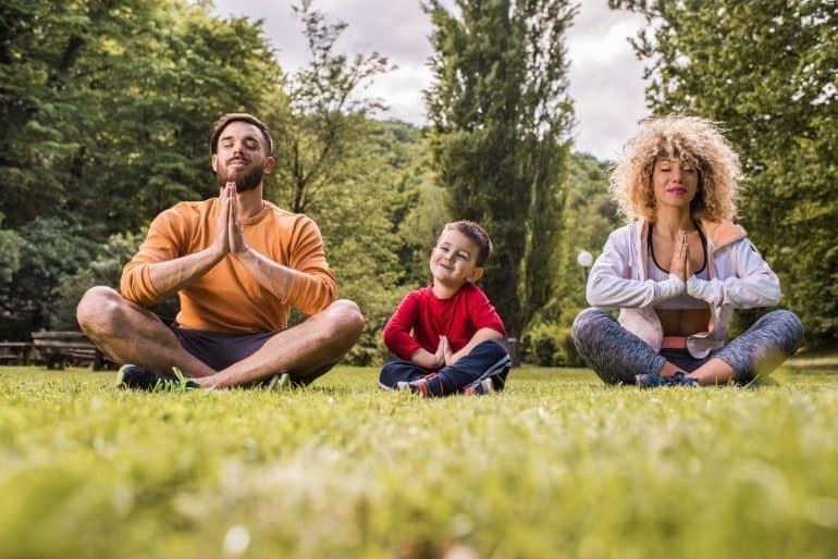 Familie versucht im Grünen achtsam zu atmen
