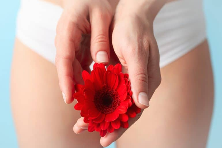 Frau hält eine rote Blume