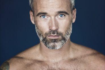 Mann mit nacktem Oberkörper steht vor einer blauen Wand