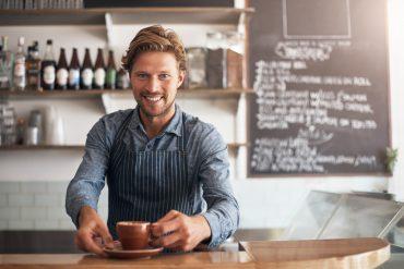 Barista mit einer Tasse Kaffee und mit einer Schürze an