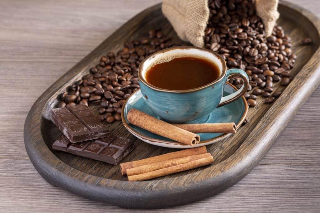 Eine Tasse aromatischer, schwarzer Kaffee mit Kaffeebohnen