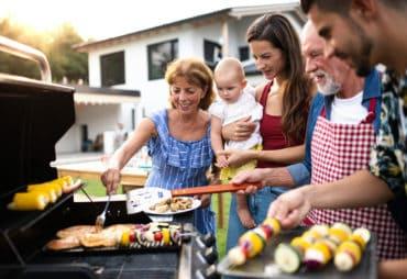 Eine Familie mit Kleinkind grillt zusammen im Sommer